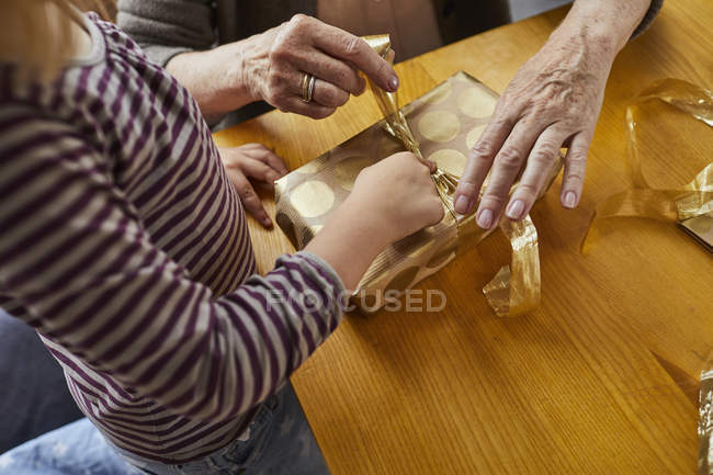 Cropped view of grandmother and granddaughter wrapping Christmas present indoors. — Stock Photo