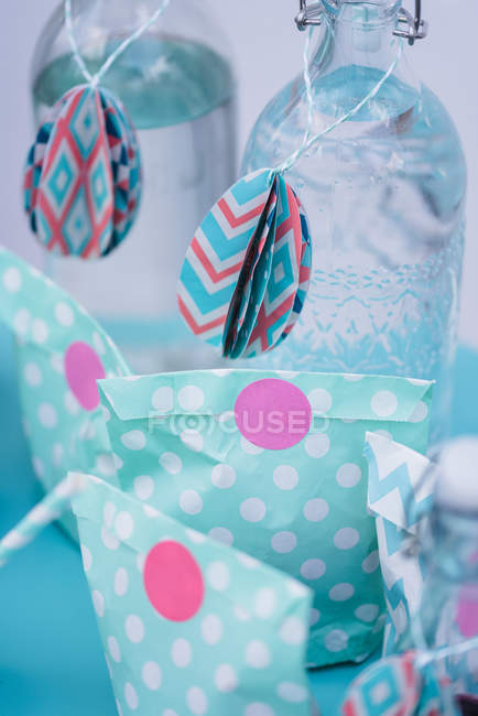 Easter decoration with colorful paper bags on bottles — Stock Photo
