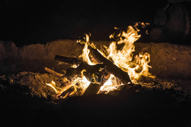 Close-up of fireplace flame and burning wood at night outdoors — Stock Photo