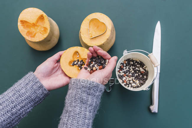 Detail of hands of woman filling pumpkins with birdseeds. — Stock Photo