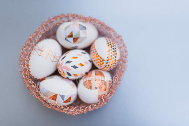Geometrical painted Easter eggs in decorative nest on grey background — Stock Photo