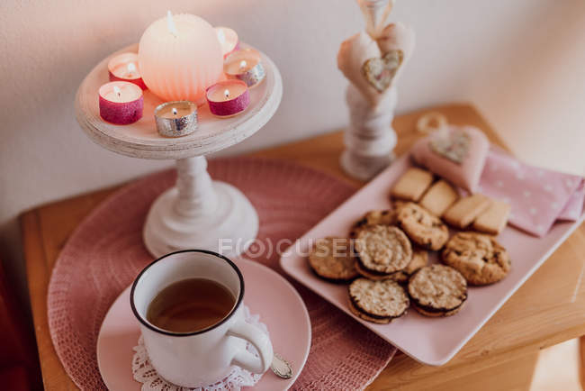 Still life with cup of hot tea, cookies and candles on wooden bedside table — Stock Photo