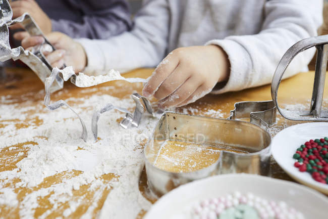 Cropped view of girls playing with cookie cutters and flour. — Stock Photo