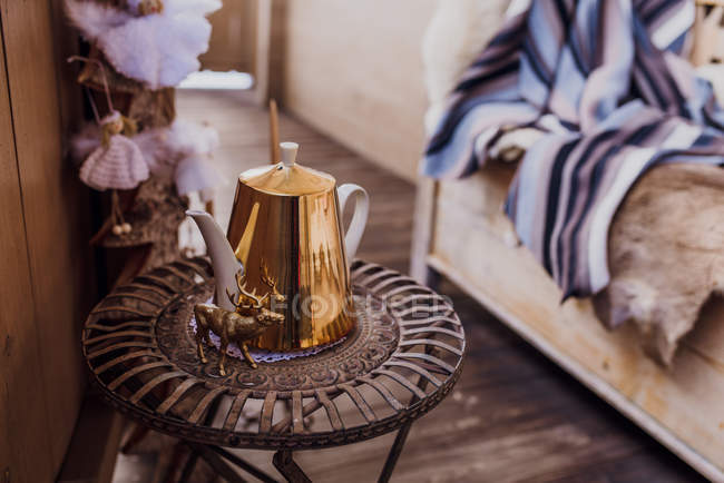 Close-up of balcony side table with golden teapot and deer figurine. — Stock Photo