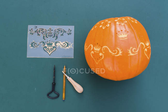 DIY autumnal carved pumpkin with stencil and tools — Stock Photo