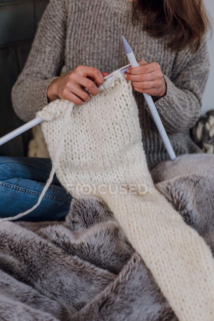 Cropped view of woman knitting scarf on bed with fur blanket — Stock Photo