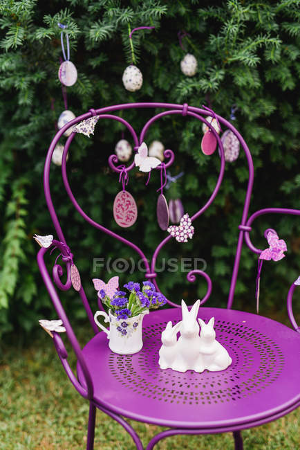 Easter decoration with garden chair and porcelain figure of Easter bunnies — Stock Photo