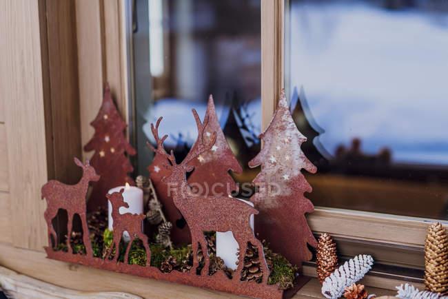 Décoration de fenêtre avec chandeliers et cônes avec des figures de cerfs — Photo de stock