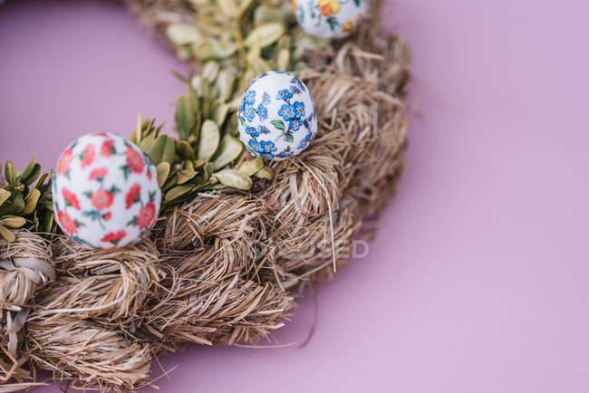 Пасха оформленный сено венок с красочные окрашенные яйца на розовом фоне — стоковое фото
