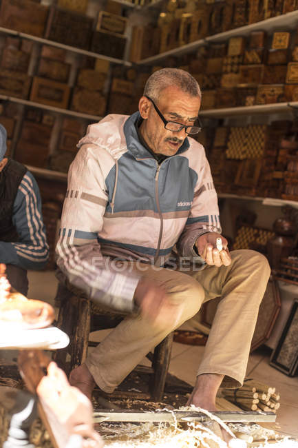 Senior craftsman woodworking in traditional workshop in Marrakesh, Morocco — Stock Photo