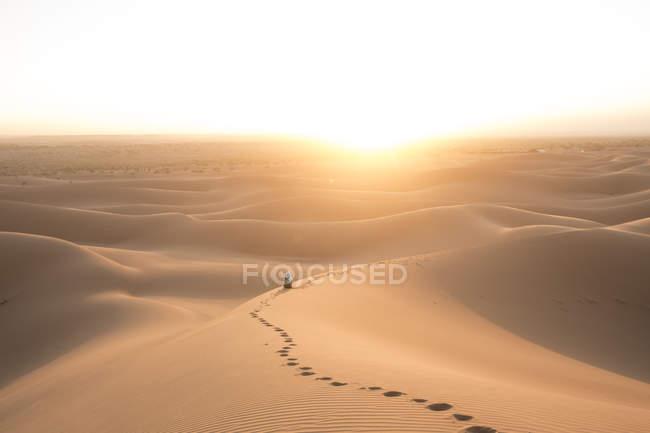 Empreintes dans les dunes de sable et touristique s'asseoir et regarder le coucher du soleil, Sahara désert, Erg Chegaga, Maroc, Afrique du Nord-Ouest — Photo de stock
