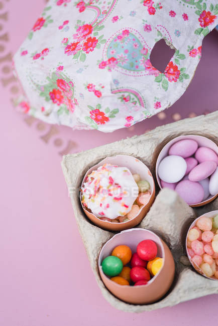 Eggshells filled with sweets and candies, still life — Stock Photo