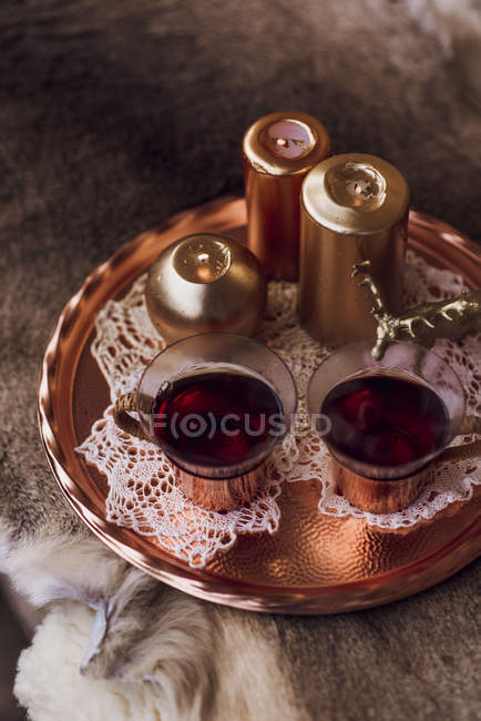 Tray with candles and teacups on fur blanket — Stock Photo
