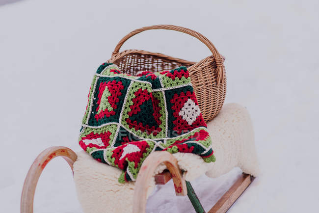 Sledge with wicker basket, knitted blanket and fur in snow — Stock Photo