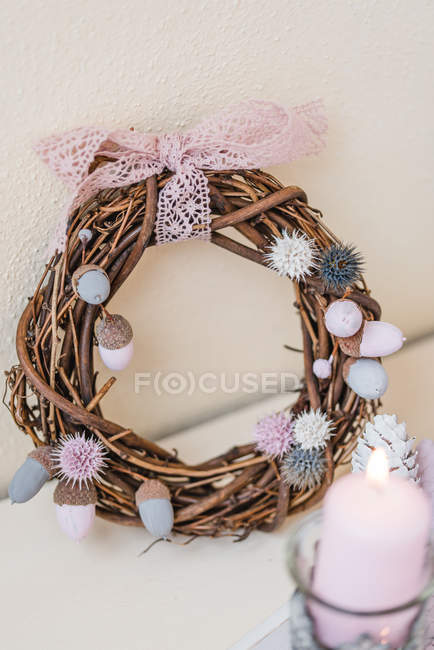 Autumnal decoration of willow wreath with acorns, thistles, ribbon in pastel colors — Stock Photo