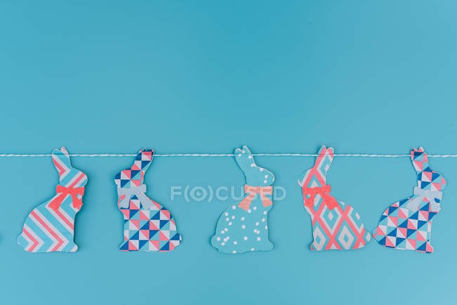 Easter decoration of bunnies garland on blue wall — Stock Photo