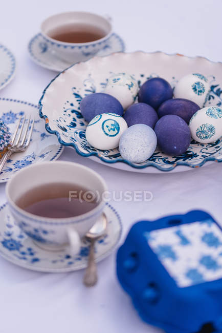 Easter table with eggs and tableware in blue — Stock Photo