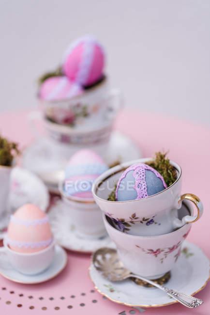 Порцелянові чашки з Великоднем оформлені барвисті яйця на рожевий таблиці — стокове фото