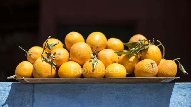Freshly harvested oranges on rustic tray — Stock Photo