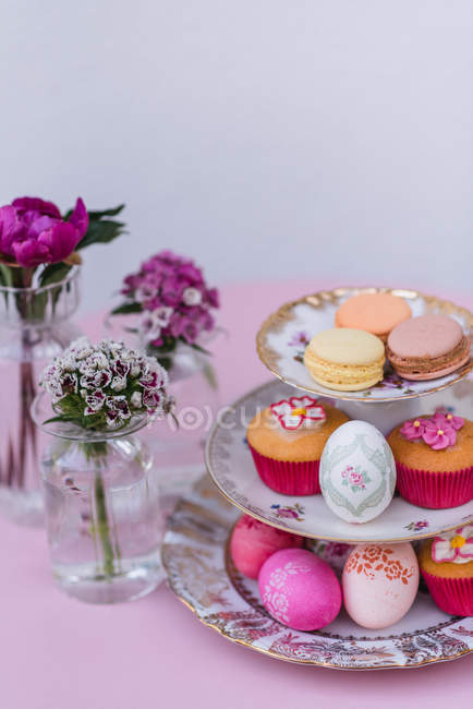 Decorated easter eggs with macarons and muffins on plates etagere on pink background with vases of flowers — Stock Photo