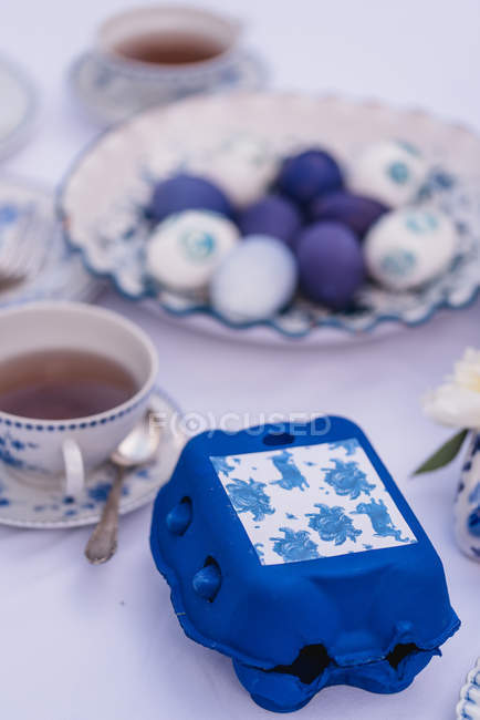 Easter table with blue egg box and colored Easter eggs — Stock Photo