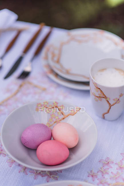 Covered table for Easter with colorful eggs and tableware — Stock Photo