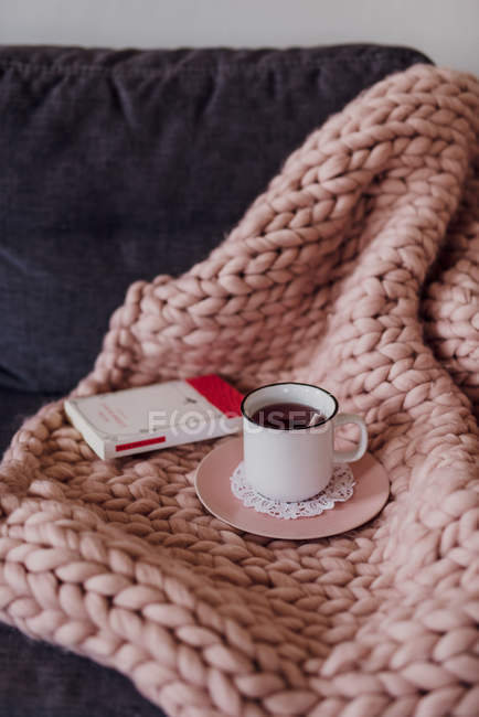 Sofa with knitted blanket, teacup and book — Stock Photo