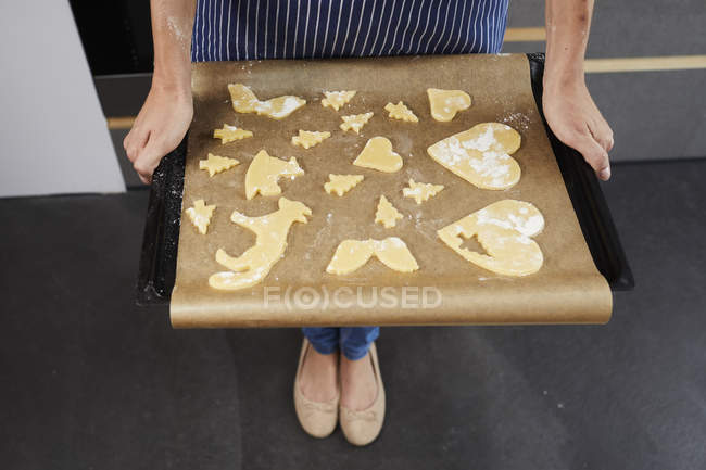 Cropped view of woman holding baking tray with uncooked Christmas cookies. — Stock Photo