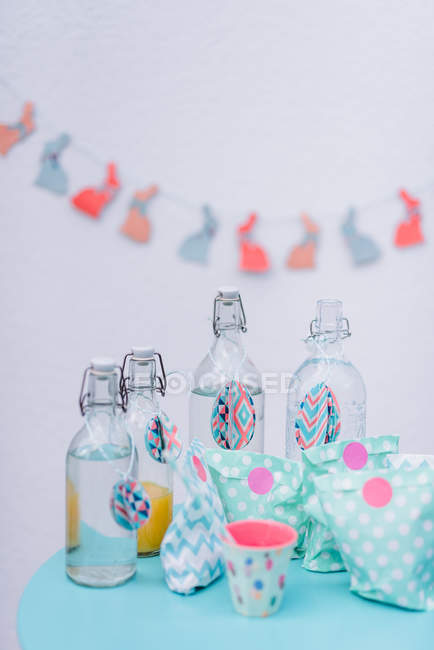 Easter decoration with bunnies garland, paper bags and bottles — Stock Photo