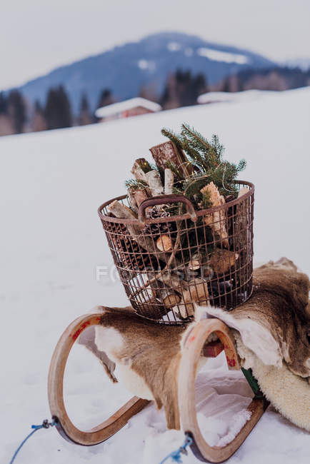 Sledge with fur and a basket of firewood — Stock Photo