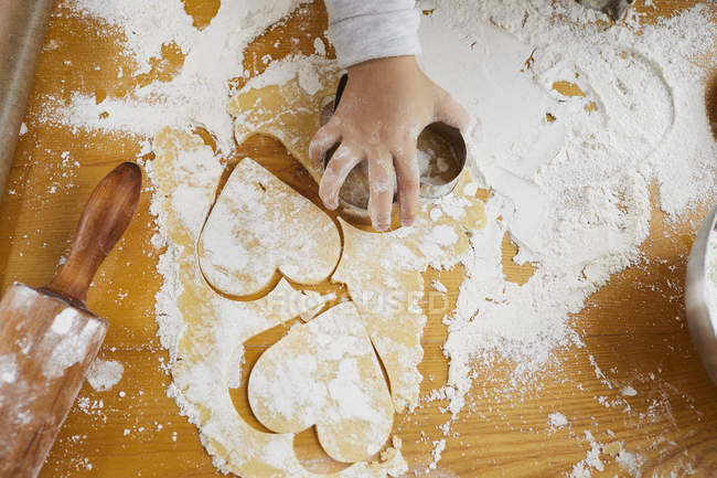 Cropped view of little girl cutting heart-shaped Christmas cookies dough with cutter. — Stock Photo