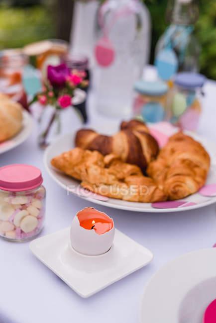 Croissants auf bunt geschmückten Ostertisch Einstellung — Stockfoto