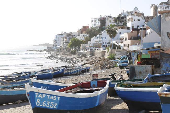 Ansicht der Küstenstadt mit traditionellen Gebäuden und blauen hölzernen Boote am Strand von Taghazout, Marokko — Stockfoto