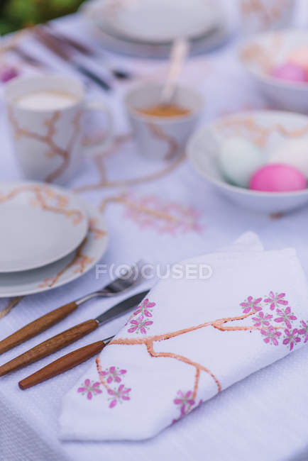 Covered table in spring mood with cutlery and colored eggs — Stock Photo