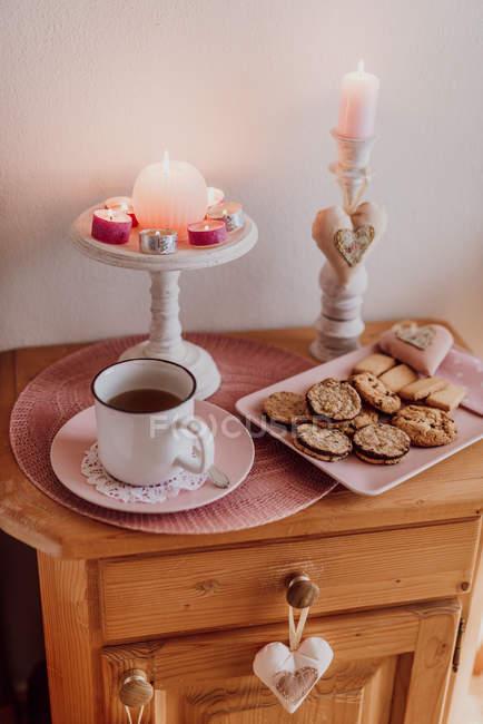 Bodegón con taza de té caliente, galletas y velas en la mesita de noche madera - foto de stock