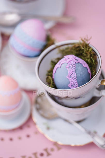 Porcelain cups with Easter decorated colorful eggs on pink table — Stock Photo