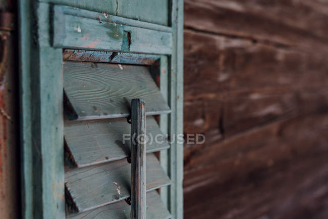 Wooden house facade with shabby shutter, detail — Stock Photo