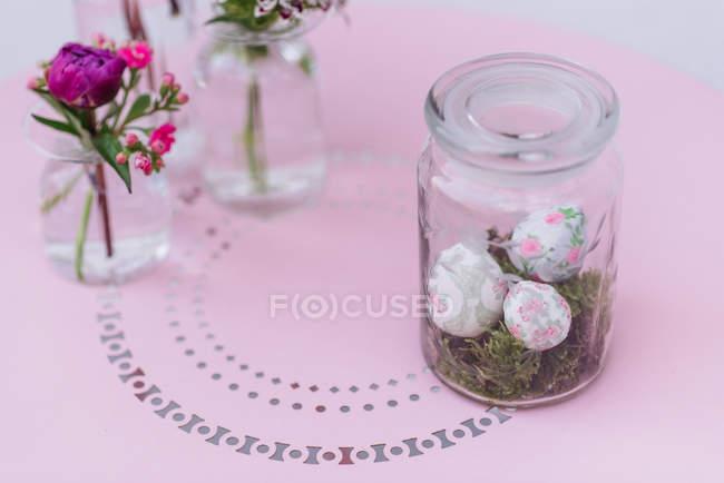 Великдень розписані яйця в банку на рожевий фон з невеликих вази квіти — стокове фото