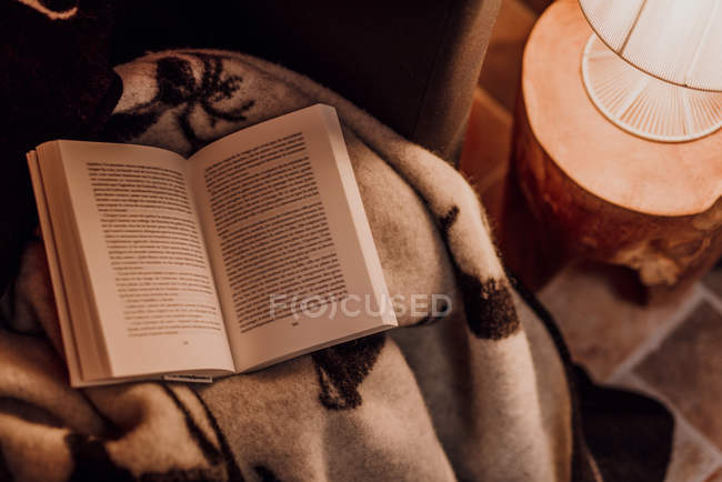 Open book on cozy blanket near lamp with warm light — Stock Photo