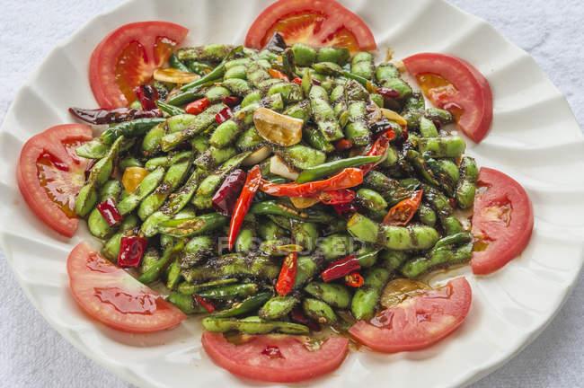 Ensalada de verduras chinas con judías verdes y tomates - foto de stock
