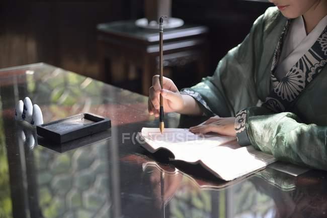 Обрізаний вид китайської жінки практикуючих каліграфія в Китаї, Азії — стокове фото