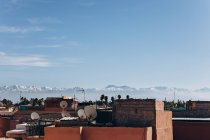 Amazing Marrakesh cityscape with traditional houses, rooftops and mountains at sunny day, Morocco, Africa — Stock Photo