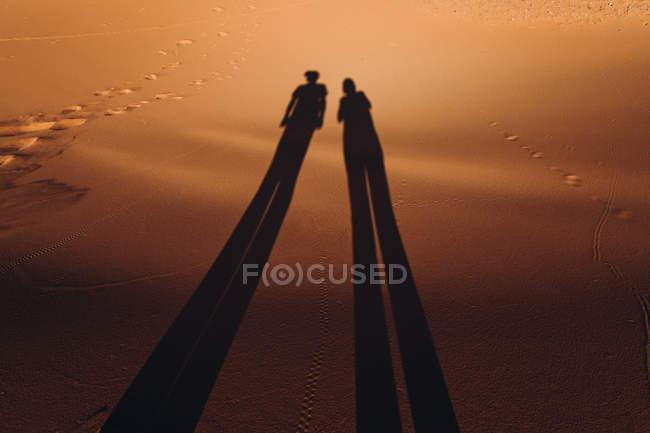 Silhouettes of couple on sand in merzouga desert, morocco — Stock Photo