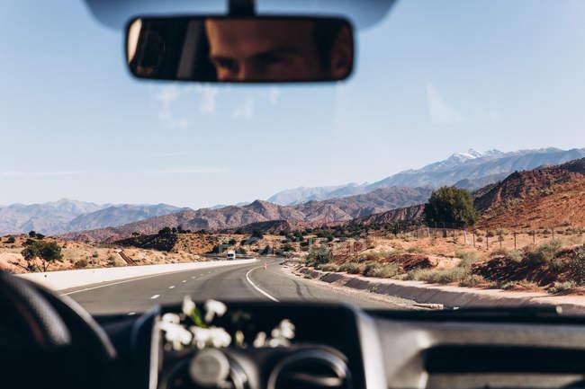 Отражение в зеркале человека за рулем автомобиля на дороге между величественными горами в Марокко, Африка — стоковое фото