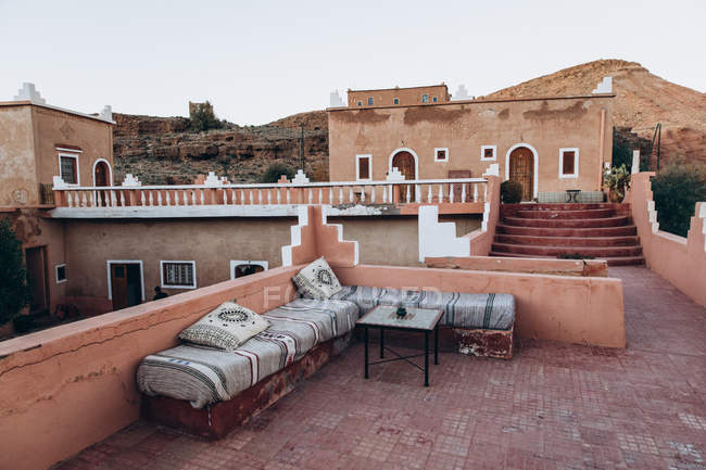 Beautiful view of old brown building and benches with pillows on terrace in Morocco, Africa — Stock Photo