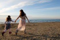 Вид сзади матери с дочерью, держащейся за руки во время прогулки по пляжу — стоковое фото