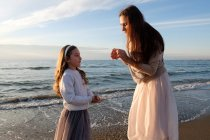 Mother with daughter standing at beach against sky with clouds — Stock Photo