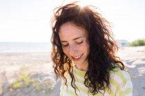 Glückliche junge Frau hört Musik am Strand, konzentriert sich auf den Vordergrund — Stockfoto