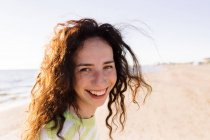 Portrait of beautiful woman with curly hair, sea in background — Stock Photo