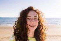 Porträt einer schönen Frau mit lockigem Haar, Meer im Hintergrund — Stockfoto